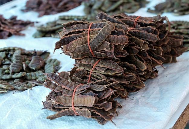 Baccelli secchi di concinna dell'acacia per vendita al dettaglio nel mercato locale della tailandia.