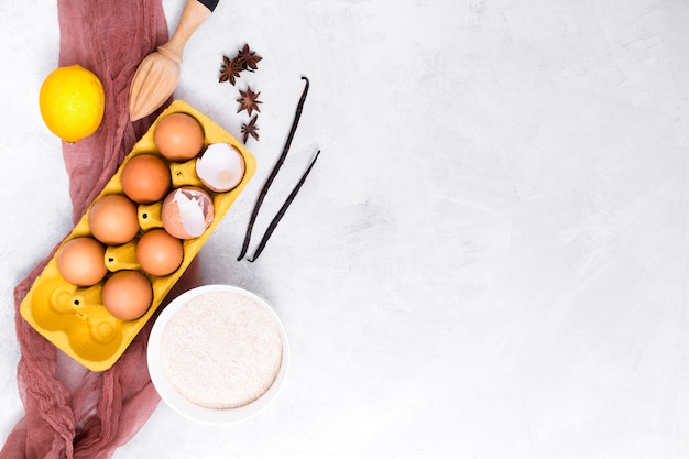 Baccello di vaniglia; uova; limone; anice stellato; farina e spremiagrumi in legno su sfondo bianco strutturato