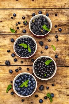 Bacche assortite nei colori blu e nero: mirtillo, mirtillo, ribes e mora. vecchio fondo di legno della tavola, fine su