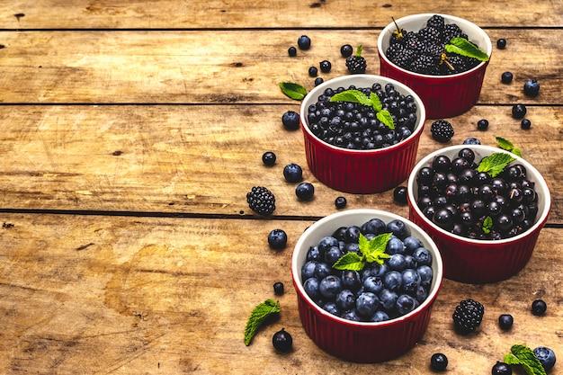 Bacche assortite nei colori blu e nero: mirtillo, mirtillo, ribes e mora. vecchio fondo di legno della tavola, spazio della copia