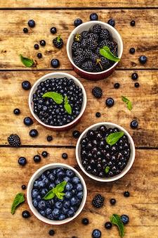 Bacche assortite nei colori blu e nero: mirtillo, mirtillo, ribes e mora. vecchio fondo di legno della tavola, vista superiore