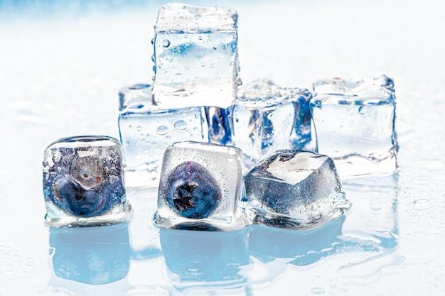 Bacche congelate in cubetti di ghiaccio sul rosa