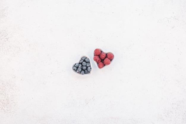 Bacche della composizione di valentine day in piatti del cuore