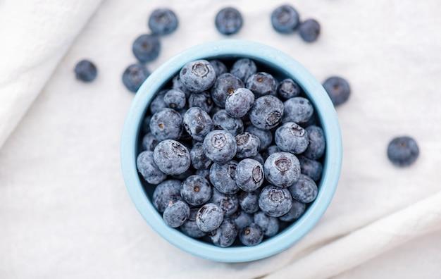 Bacche della foresta del mirtillo o del mirtillo in piatto ceramico blu sulla tovaglia bianca, vista superiore