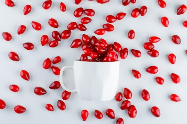 Bacche di corniolo in una tazza su bianco