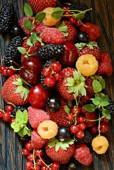 Bacche di estate su un primo piano del bordo di legno. frutti di bosco come fragole, mirtilli, ribes rosso, lamponi e more su una tavola di legno.