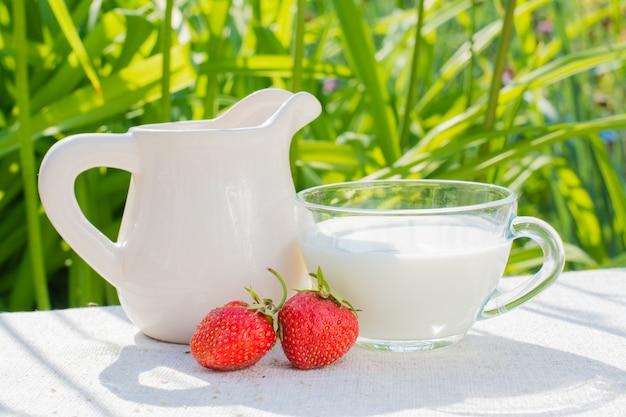 Bacche di fragola, una brocca e una tazza con latte su un tavolo di legno al sole