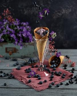 Bacche di mirtillo in una tazza di cialda circondata da fiori e bacche viola. tema estivo levitazione