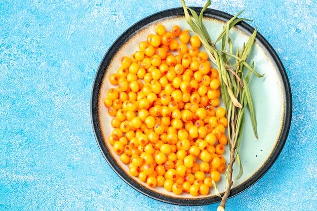 Bacche di olivello spinoso in ciotola e miele naturale o olio di olivello spinoso su sfondo blu