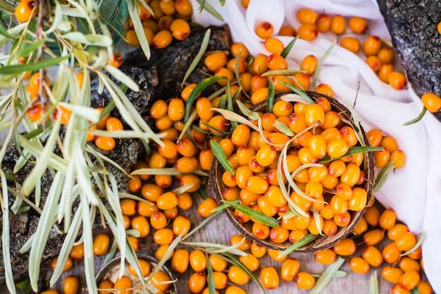 Bacche di olivello spinoso in una ciotola su un tavolo di legno. vista dall'alto
