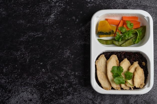 Bacche di riso viola cotte con petto di pollo grigliato foglie di zucca, carote e foglie di menta in una scatola di plastica