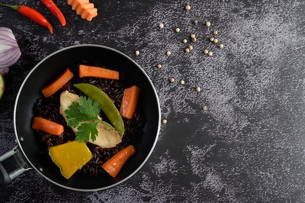 Bacche di riso viola cotte con petto di pollo grigliato. zucca, carote e foglie di menta in padelle.