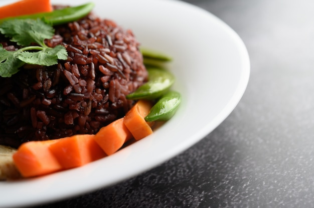 Bacche di riso viola cotte con petto di pollo grigliato. zucca, carote e foglie di menta in un piatto, cibo pulito.
