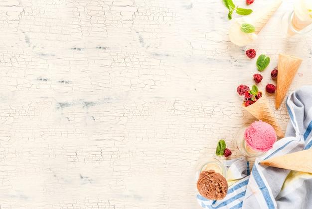 Bacche dolci e dessert estivi, vari gusti di gelato in coni rosa (lampone), vaniglia e cioccolato con menta su cemento leggero
