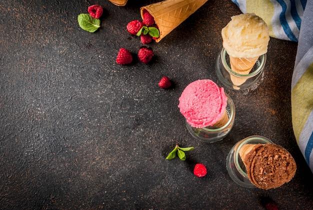 Bacche dolci e dessert estivi, vari gusti di gelato in coni rosa (lampone), vaniglia e cioccolato con menta su fondo scuro