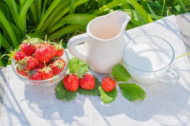 Bacche e foglie di fragola, una brocca e una tazza con latte su un tovagliolo su un tavolo di legno