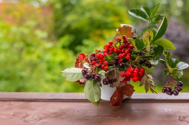 Bacche e frutti autunnali sul tavolo di legno. bacche di sorbo, bacche di chokeberry nere, viburno nel cestino