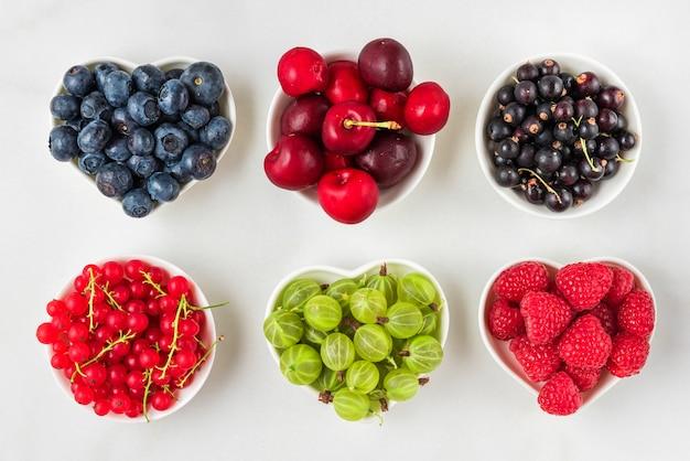 Bacche fresche di estate lampone, ciliegia, mirtillo, ribes, ribes nero e uva spina su bianco