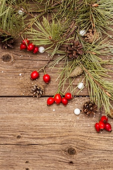 Bacche fresche di rosa canina, caramelle a forma di palla, rami e coni di pino, neve artificiale. decorazioni naturali, tavole di legno vintage