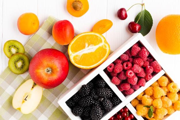 Bacche fresche piatte sulla tovaglia con frutta