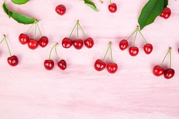 Bacche mature di ciliegia e modello luminoso colorato di foglia di ciliegia