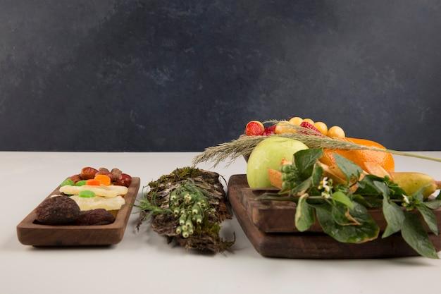 Bacche, mix di frutta ed erbe aromatiche in un piatto di legno isolato su uno spazio bianco
