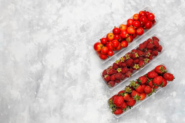 Bacche organiche fresche in scatole di plastica su calcestruzzo grigio, vista superiore, copyspace