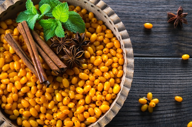 Bacche organiche fresche mature dell'olivello spinoso in ciotola di legno con i bastoni di cannella, le stelle dell'anice e la menta sulla tavola scura. ingredienti per bevande vitaminiche salutari