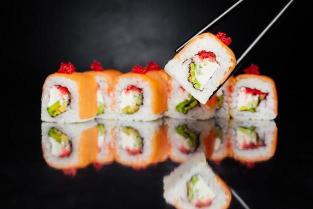 Bacchette che tengono il rotolo di sushi filadelfia su fondo nero fatto del salmone