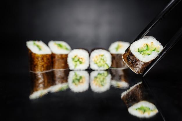 Bacchette che tengono rotolo fatto di nori, riso marinato, sesamo bianco, cetriolo.