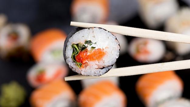 Bacchette close-up con rotolo di sushi