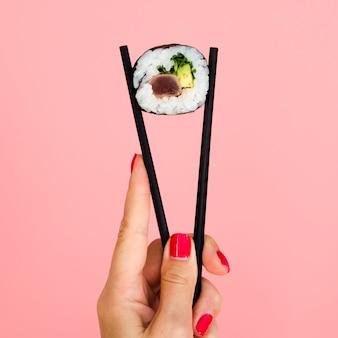 Bacchette della holding della donna con il rotolo di sushi