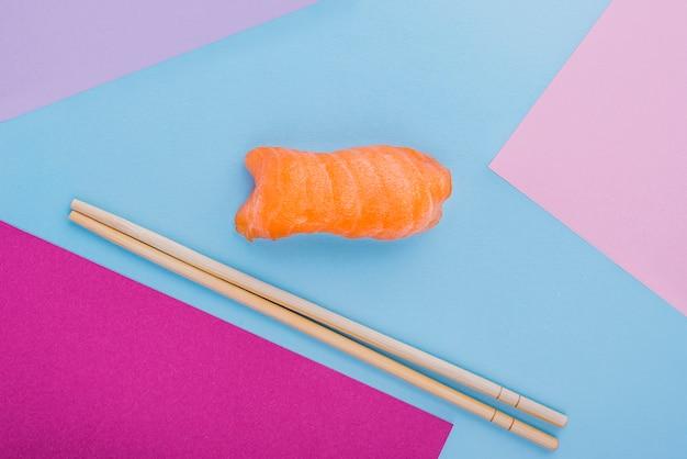 Bacchette e rotolo di sushi