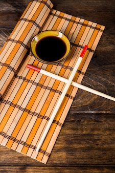 Bacchette incrociate e ciotola di salse di soia su placemat sopra la scrivania di legno