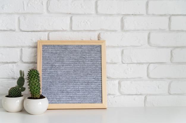 Bacheca grigia in feltro quadrato con piccole piante grasse sul muro di mattoni bianchi