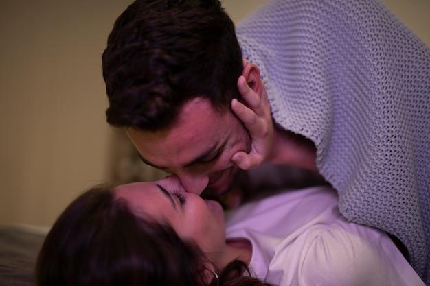 Baciare felice delle giovani coppie del primo piano
