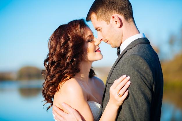 Baciare la sposa e lo sposo nel giorno delle nozze vicino all'albero di autunno