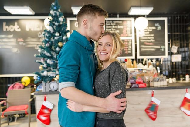 Baciare le giovani coppie vicino all'albero di natale in caffè