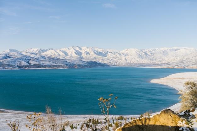 Bacino idrico di charvak in uzbekistan in inverno con acqua blu al suo interno, circondato dal sistema montuoso tien shan