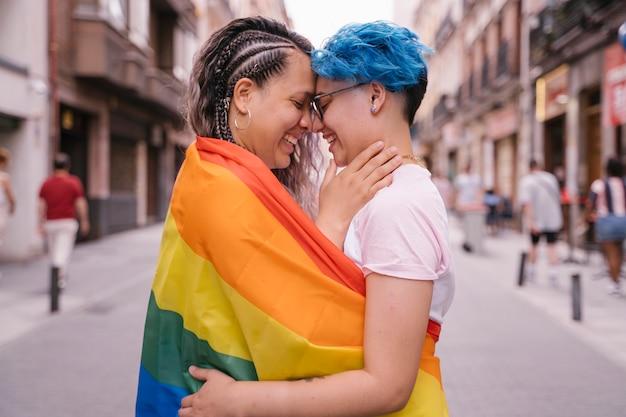 Bacio affettuoso tra due donne avvolte in una bandiera gay.