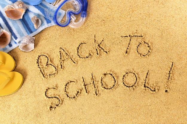 Back to school scritto su una spiaggia