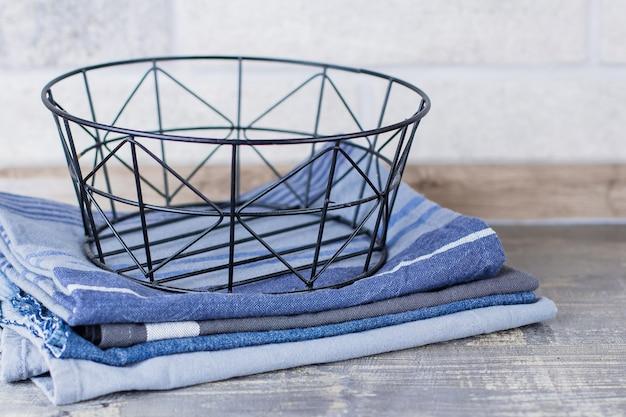 Backet di metallo e asciugamani da cucina e tovaglioli su un tavolo