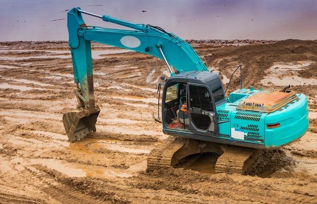 Backhoe scavando il terreno per costruire una strada fluviale lungo il fiume