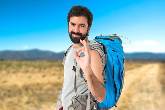 Backpacker che fa ok segno su sfondo bianco