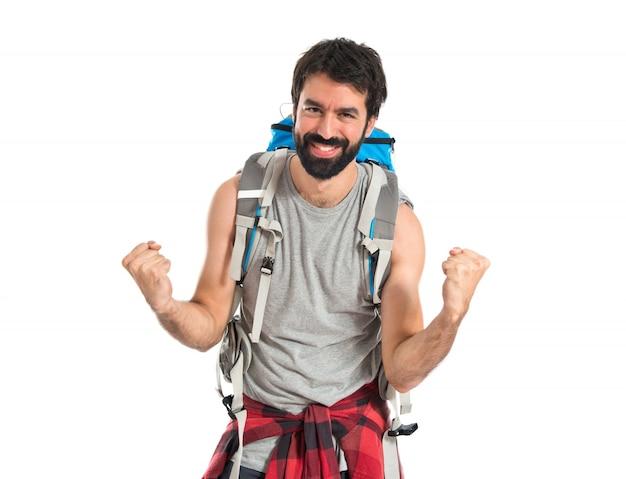 Backpacker fortunato su sfondo bianco isolato