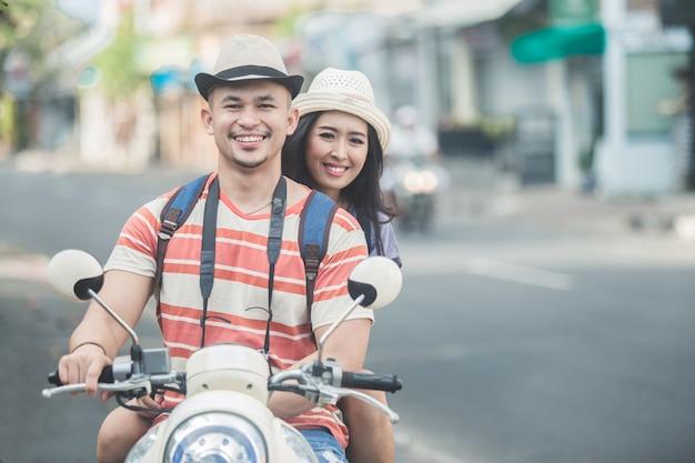 Backpackers coppia in sella a una moto per iniziare il loro viaggio