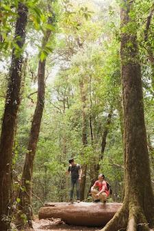 Backpackers in piedi sul tronco d'albero
