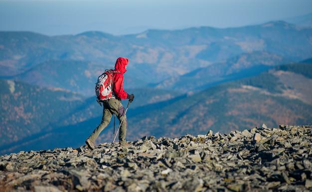 Backpaker maschio che cammina sulla cima rocciosa della montagna