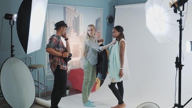 Backstage del servizio fotografico: fotografo con assistente che sceglie i vestiti per il servizio fotografico della modella