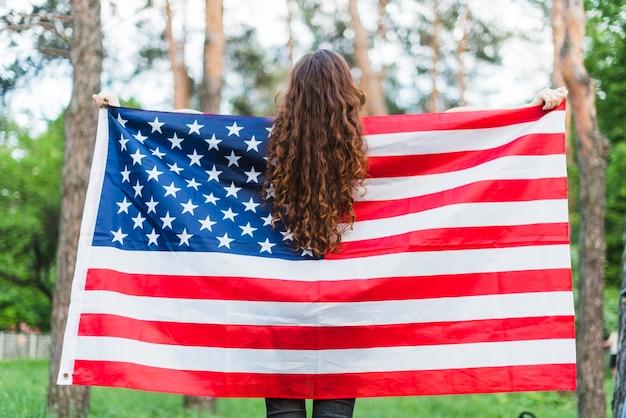 Backview della ragazza con la bandiera americana in natura